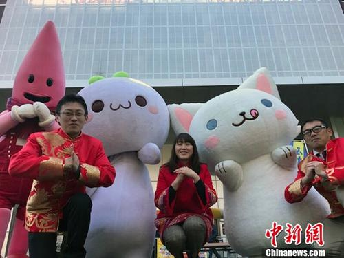 """今年春节期间,由中国十二栋文化公司创作的微信动态表情包""""长草颜团子""""在东京塔举行春节活动。图为日本当地活动组织者与团子人偶等在东京塔合影。中新社记者 钟欣 摄"""