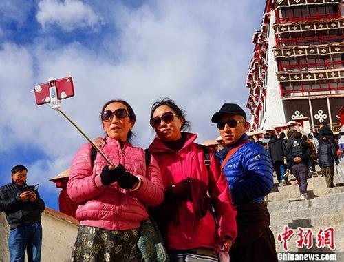 """自2月1日""""冬游西藏・共享地球第三极""""活动启动以来,一系列优惠政策掀起了西藏冬季旅游的热潮。图为游客在布达拉宫拍照留念。&#10;<a target='_blank' href='http://www.chinanews.com/'>中新社</a>记者 赵延 摄"""
