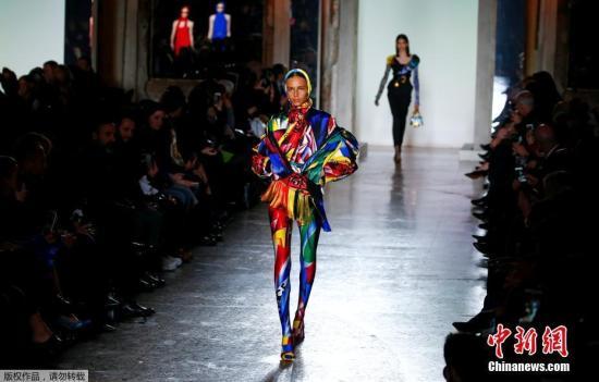 资料图:米兰时装周上,模特身着华服登台表演。