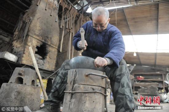 铁匠传承人牛祺圣在家里制作铁锅。图片来源:视觉中国