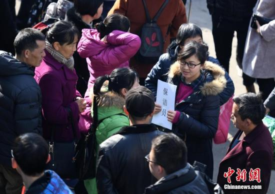 """2月24日,四川成都,劳务市场内一位拿着写有招保洁员的雇主正在寻找合适的工人。当日,成都市锦江区人力资源市场持续迎来春节后务工求职高峰,市场内写有求职意向内容的""""榜单""""摆满,但现场招工的雇主并不是很多。 <a target='_blank' href='http://www-chinanews-com.look189.com/'>中新社</a>记者 刘忠俊 摄"""