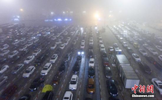 2月25日凌晨,海口市区再次出现浓雾天气,海口市气象台发布大雾橙色预警。受大雾天气影响,能见度低,琼州海峡再次全线停航,暂停船舶进出港。深夜下的海口秀英港、新海港、南港港区内外依然有8000余辆滞留车辆排队等待过海。图为航拍海口秀英港码头内排队等待过海的车辆。中新社记者 骆云飞 摄
