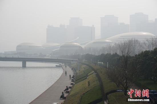 在于郑州如意湖畔的河南艺术中心,于霾中若隐若现。董飞 照