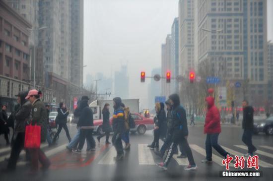 2月28日,辽宁沈阳,市民在雨夹雪的天气出行。预计辽宁还将出现大范围雨雪寒潮天气,局地有大雪到暴雪。降水过后,各地气温下降8~10℃,并伴有大风天气。中新社记者 于海洋 摄