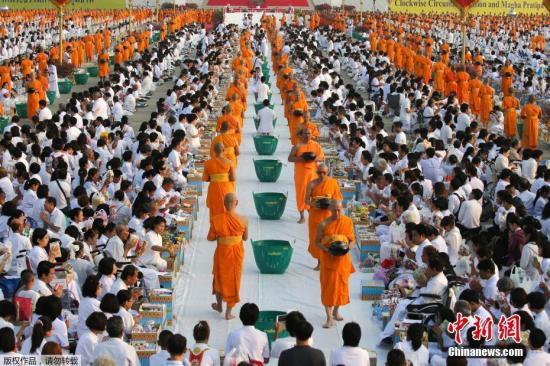 """当地时间3月1日,泰国庆祝万佛节活动在巴吞他尼府举行,佛教僧侣在最大佛寺之一法身寺参加""""布施""""仪式。万佛节是泰国的传统佛教节日,在每年泰历三月十五日举行。相传佛教创始人释迦牟尼于泰历三月十五日在摩揭陀国王舍城竹林园大殿,向前来集会的1250名罗汉首次宣传教义,故称其为四方聚集的集会。笃信小乘佛教的泰国佛教徒将该次集会视为佛教创建之日,每年都在这一天进行隆重庆祝、纪念。泰国的佛教徒早在阿育陀耶王朝时期就开始纪念万佛节,至曼谷王朝五世王时,官方开始举行庆祝仪式,并于1913年将这一天定为节假日并成为泰国人民传统的佛教节。"""
