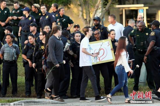 资料图:2月28日,美国佛罗里达州帕克兰发生枪击案的道格拉斯中学复课,学生和教职工重返校园,大批警察出动维护治安。