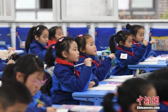 资料图:小学生们正在课堂内认真听讲。/p中新社记者 王刚 摄