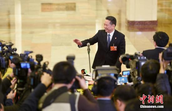 """3月5日,交通运输部部长李小鹏在十三届全国人大一次会议的""""部长通道""""承受媒体采访。 中新社记者 侯宇 摄"""