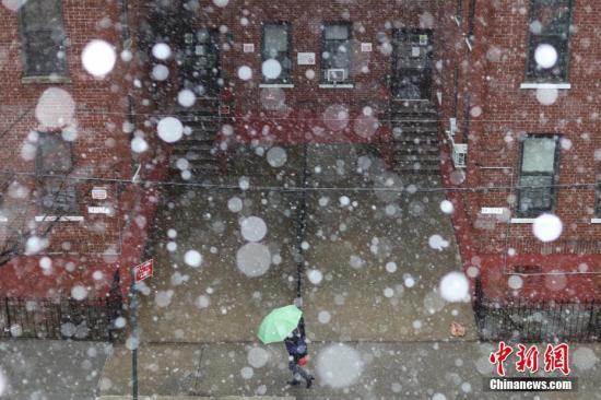 资料图:当地时间3月7日,美国纽约降下大雪,法拉盛社区民众在雪中前行。中新社记者 廖攀 摄