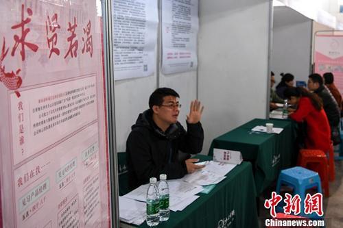 资料图:3月9日,一企业的招聘人员挥手招揽求职者。<a target='_blank' href='http://www.chinanews.com/'>中新社</a>记者 杨华峰 摄
