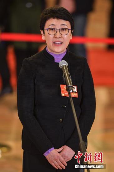 """3月10日下午,全国政协十三届一次会议在北京人民大会堂举行第二场""""委员通道""""集中采访活动。图为全国政协委员、住房与城乡建设部副部长黄艳接受采访。 <a target='_blank' href='http://www-chinanews-com.biao166.cn/'>中新社</a>记者 骆云飞 摄"""