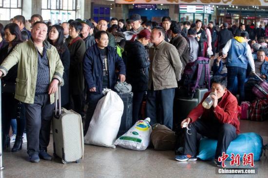 3月12日,山西太原,民众正准备乘车出行。当日,为期40天的中国春运正式结束。图为民众在候车室等待检票乘车。张云 摄