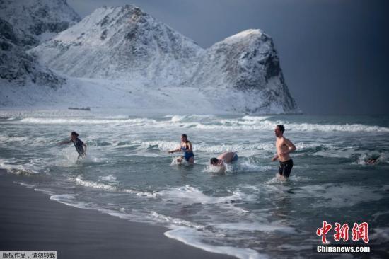 """资料图:在北极圈附近的罗弗敦群岛,一群游客正愉快地""""冬泳""""。"""