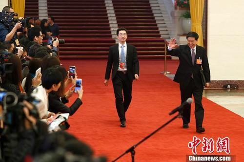 """3月13日,国家税务总局局长王军(右一)在十三届全国人大一次会议的""""部长通道""""接受媒体采访。中新社记者 富田 摄"""