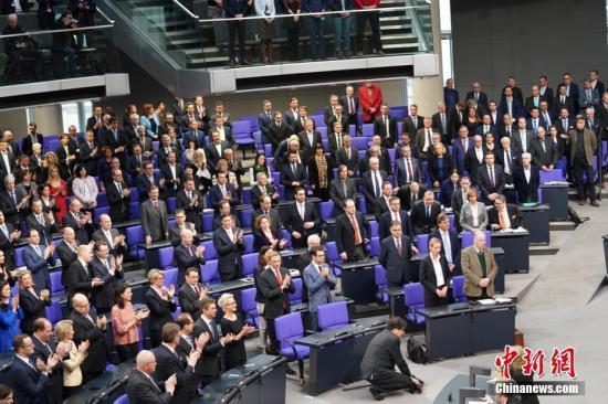 资料图:当地时间3月14日,德国联盟党领袖默克尔在柏林的联邦议院内面对联邦议长朔伊布勒宣誓就职新一任德国总理。这开启了她作为德国首位女总理的第四个任期。本次德国完成组阁距离2017年9月大选已近半年,下一次德国大选将于2021年举行。图为默克尔宣誓完毕后在场的联盟党和自民党议员鼓掌祝贺。记者 彭大伟 摄