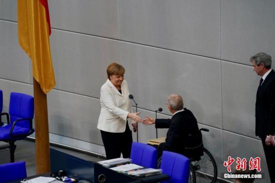 当地时间3月14日,德国联盟党领袖默克尔在柏林的联邦议院内面对联邦议长朔伊布勒宣誓就职新一任德国总理。这开启了她作为德国首位女总理的第四个任期。本次德国完成组阁距离2017年9月大选已近半年,下一次德国大选将于2021年举行。图为默克尔宣誓完毕后与朔伊布勒握手。<a target='_blank' href='http://www.chinanews.com/'>中新社</a>记者 彭大伟 摄