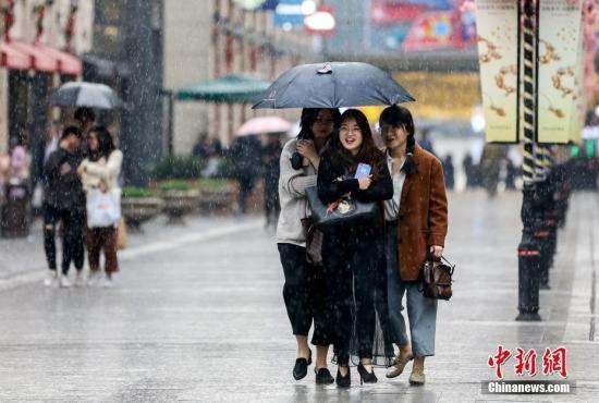 资料图:民众在雨中出行。中新社记者 张畅 摄