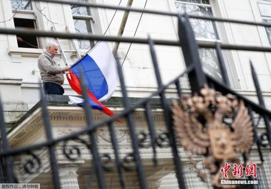 当地时间2018年3月14日,一名男子将俄罗斯驻英国大使馆门前的俄罗斯国旗取下。 近日,俄罗斯前情报人员斯克里帕尔与其女儿在伦敦某商场内接触不明物质后当场倒下。随后,这一事件引发英俄外交风波。