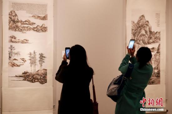 """3月16日,由中国美术馆、香港中文大学文物馆团结主理的""""自吾有乾坤——吕寿琨与早期水墨行动""""展览在中国美术馆开幕。此次展览从香港中文大学文物馆及香港艺术馆提选出了51件上世纪40年代末至70年代初吕寿琨最具代外性的作品。图为参不益看者用手机拍摄作品。中新社记者"""
