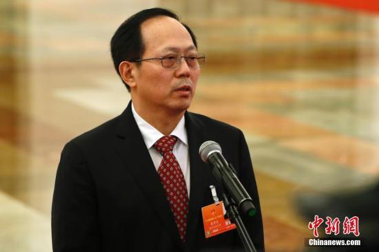 """3月19日,十三届全国人大一次会议在北京人民大会堂举行第七次全体会议。国家体育总局局长苟仲文在""""部长通道""""接受采访。 记者 富田 摄"""