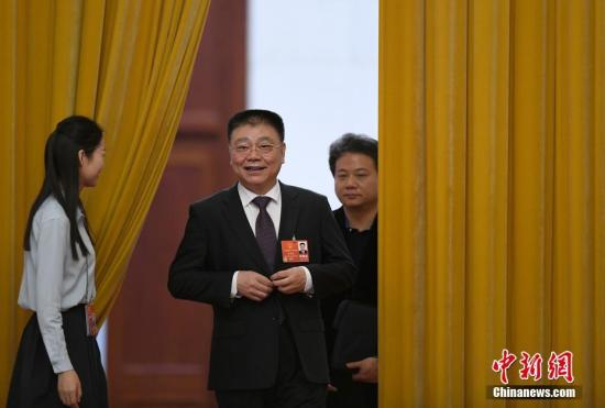 """3月19日,十三届全国人大一次会议在北京人民大会堂举行第七次全体会议。图为住房和城乡建设部部长王蒙徽步入""""部长通道""""接受采访。 记者 侯宇 摄"""