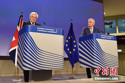 """当地时间3月19日,脱欧谈判欧盟首席谈判代表巴尼耶(图右)与英国脱欧事务大臣戴维斯(图左)共见记者,宣布双方迈出""""决定性一步"""",就脱欧过渡期安排等议题达成协议,但棘手的英国北爱尔兰与爱尔兰边界问题仍悬而未决。<a target='_blank' href='http://www.chinanews.com/'>中新社</a>记者 德永健 摄"""
