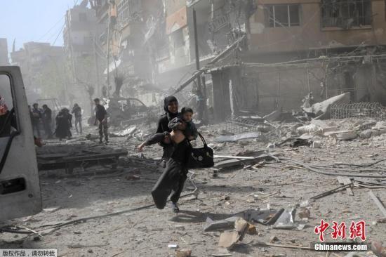 当地时间2018年3月20日,叙利亚东古塔地区当地再遭政府军空袭,一名妇女抱着孩子在废墟上狂奔。
