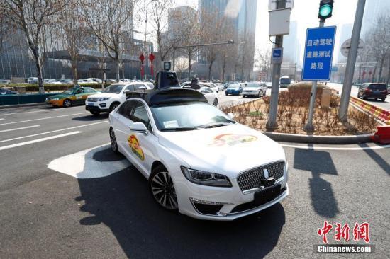 """3月22日,北京官方发放京城首批自动驾驶测试试验用临时号牌,并在五环外确定了33条共计105公里的首批开放测试道路。当日,有3辆自动驾驶测试车辆""""领证""""后在北京经济技术开发区正式上路测试。同时,北京市对自动驾驶车辆的测试要求做出进一步细化,上路前须在封闭场地训练5000公里以上。测试道路的选址都在五环以外,仅在白天测试,将避开早晚高峰和夜间时段,还会避开住宅区、办公区、医院、学校等人流量车流量集中的区域,并张贴醒目的自动驾驶测试车身标识,以便于民众识别。<a target='_blank' href='http://www.chinanews.com/'>中新社</a>记者 富田 摄"""
