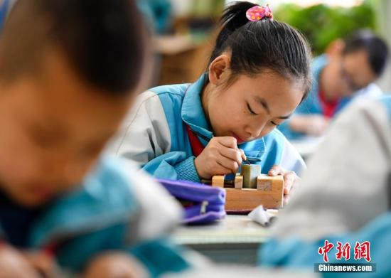 资料图:小学生在专业老师的指导下练习篆刻艺术。中新社记者 刘新 摄