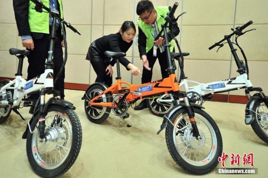 资料图:观众在观看磁动力循环自供电系统的电动自行车。 <a target='_blank' href='http://www.chinanews.com/'>中新社</a>记者 佟郁 摄