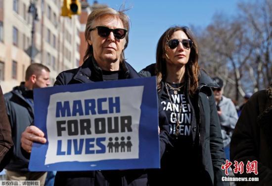 """纽约民众也举着以往校园枪击案受害师生的肖像和生平介绍,参加活动。图为前""""披头士""""乐队成员保罗・麦卡特尼在纽约参加反枪支游行。"""