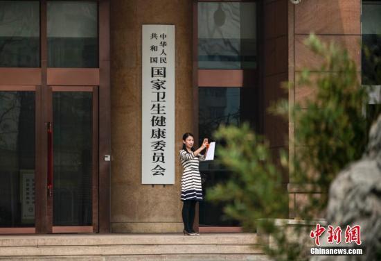 3月27日,新组建的中国国家卫生健康委员会在北京正式挂牌,工作人员与新牌合影。<a target='_blank' href='http://www.chinanews.com/'>中新社</a>记者 贾天勇 摄