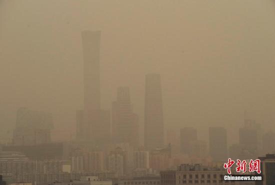 资料图:北京CBD地区的高层建筑笼罩在雾霾和扬沙天气中。 中新社记者 贾天勇 摄