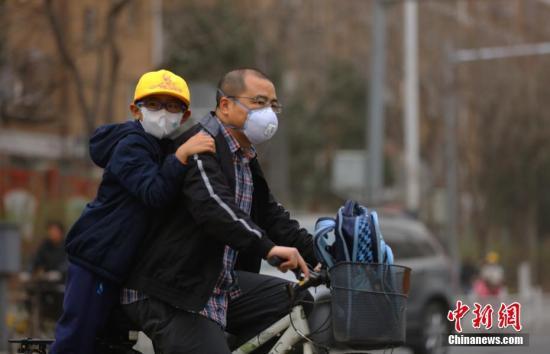 """3月28日,北京民众戴口罩在街头出行。当日,雾霾沙尘齐聚京城,除此前启动的空气重污染橙色预警之外,官方还发布了今年首个沙尘蓝色预警。在两者""""夹攻""""之下,全城空气质量已达到严重污染水平。 <a target='_blank' href='http://www.chinanews.com/'>中新社</a>记者 杨可佳 摄"""