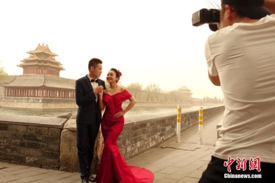 3月28日,雾霾沙尘齐聚京城,除此前启动的空气重污染橙色预警之外,官方还发布了今年首个沙尘蓝色预警,空气质量已达到严重污染水平。图为一对情侣在北京故宫附近拍摄婚纱照。 <a target='_blank' href='http://www.chinanews.com/'>中新社</a>记者 杜洋 摄
