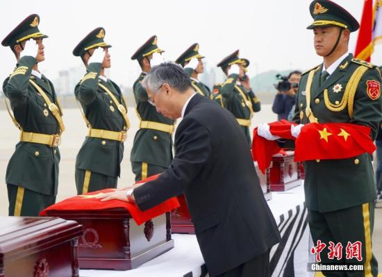图为中国驻韩国大使邱国洪为志愿军烈士遗骸覆盖国旗。 中新社记者 吴旭 摄