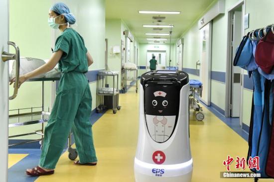4月3日,AI(人工智能)医生助手为医生运送手术所需工具。近日,广州首个智慧医院在广东省第二人民医院上线,为市民提供智能问诊、手机挂号支付、科室导航等服务,并为医生提供AI(人工智能)医生诊断、智能运输器材等协助。中新社记者 陈骥�F 摄