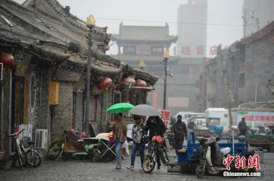 4月3日,雪中的明清古街,民众撑伞步行。当日,呼和浩特迎来降雪,气温骤然下降,不少民众纷纷加衣保暖。中新社小编 刘文华 摄