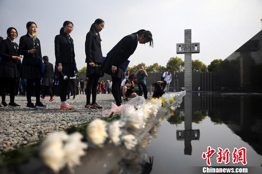 资料图:中学生向南京大屠杀遇难同胞纪念碑鞠躬。 泱波 摄
