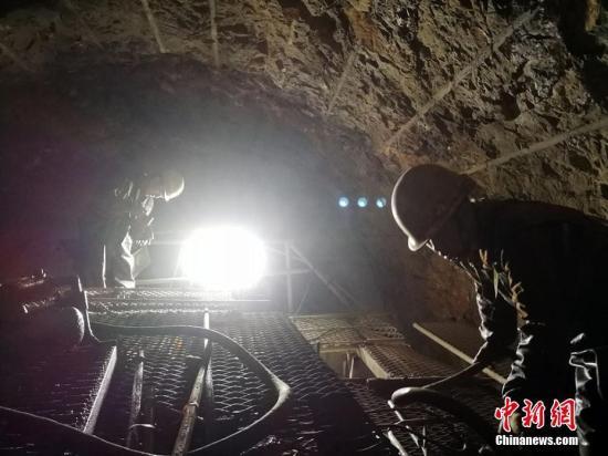 其中阿尔金山隧道(13.195千米)为全线第一长隧、重点控制性工程,全线唯一一座一级风险隧道。合同工期57个月,完工日期2020年9月30日。图为隧道内工人依靠灯光作业。 王小军 摄