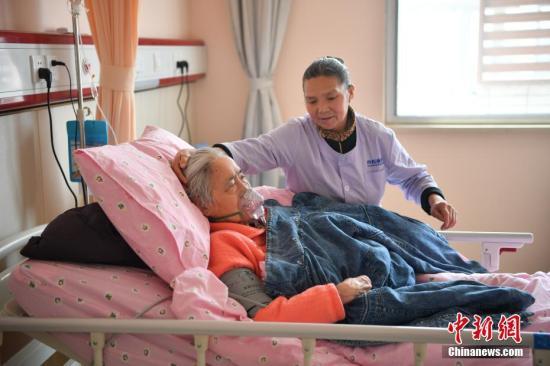 """经过半年的发展,缓和医学中心发展迅速,被业内称为""""缓和医学的昆明模式"""",经常有慕名而来的同行到此拜访学习。图为4月3日,护工精心照料住院病患。 中新社记者 刘冉阳 摄"""