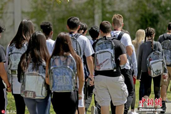 资料图:当地时间2018年4月2日,美国帕克兰道格拉斯高中的学生背着透明书包上学。该高中2月份发生校园枪击案,17人丧生。为了加强安全管制,该校规定,所有学生今后只能携带校方提供的透明书包上学。 图片来源:东方IC 版权作品 请勿转载