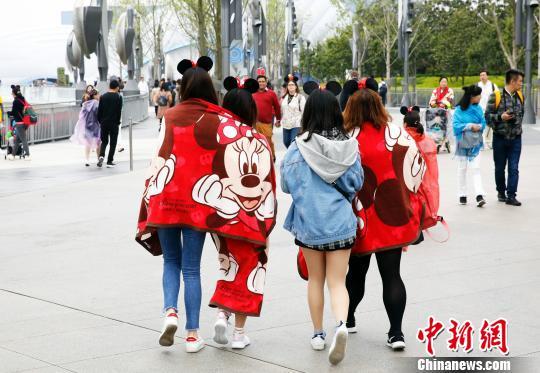 资料图:上海气温骤降,游客将迪士尼绒毯包裹在身上抵御寒风。汤彦俊 摄