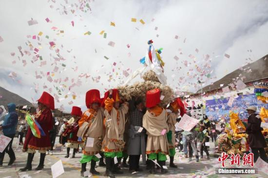 """4月7日是藏历二月二十二日,青海省玉树藏族自治州称多县古村落卓木齐藏族民众迎来传统""""糌粑节"""",村中男女老少以""""糌粑大战""""形式互表祝福。据了解""""糌粑节""""为当地传统的春耕祭祀仪式,已传承千年。图为""""糌粑节""""迎请""""白色神鸟仪式,民众抛撒龙达。 中新社记者 罗云鹏 摄"""