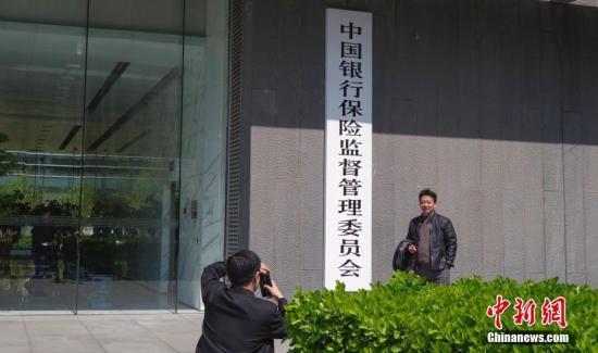4月8日,中国银行保险监督管理委员会在北京正式挂牌,民众与新牌合影。中新社记者 贾天勇 摄