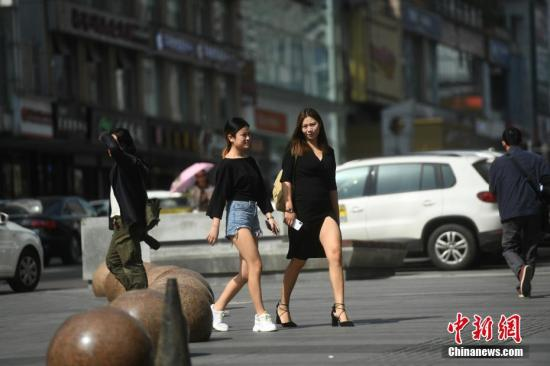 资料图:重庆市民着凉装出行。陈超 摄