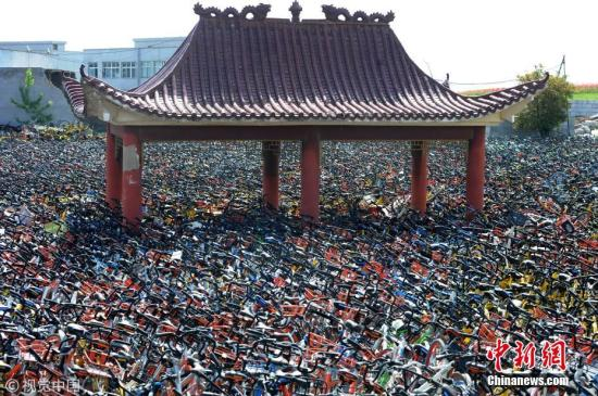 """资料图:武汉一空地上堆满共享单车,凉亭变""""孤岛""""。图片来源:视觉中国"""