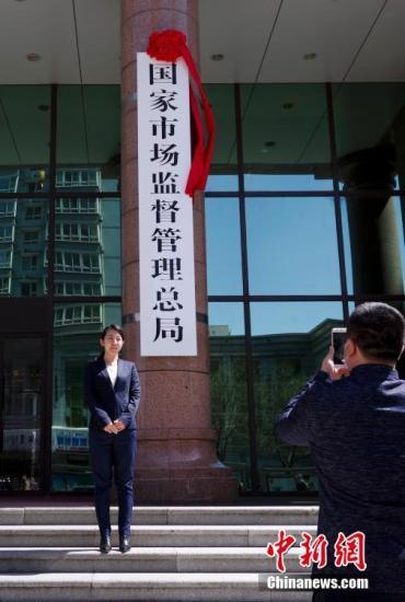 4月10日,新组建的国家市场监督管理总局在北京正式挂牌。图为民众与新牌合影。 <a target='_blank' href='http://www.chinanews.com/'>中新社</a>记者 贾天勇 摄