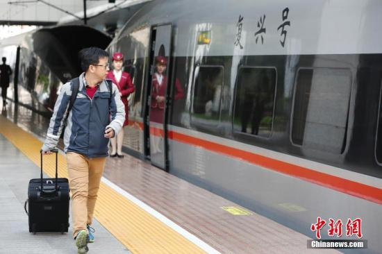 """4月10日,列车员在""""复兴号""""列车旁迎接旅客的到来。当日上午,从上海站始发的G6次""""复兴号""""高铁列车驶出站台,向目的地北京开行,这是上海站首开""""复兴号""""京沪高铁。10日零时起,中国铁路实行新的列车运行图。新图实施后,上海至北京间的""""复兴号""""京沪高铁列车将从原来的7对增加到10对,其中2对为上海站始发,8对为上海虹桥站始发,北京至上海间实现最快4小时18分可达。 <a target='_blank' href='http://www.chinanews.com/'>中新社</a>记者 殷立勤 摄"""