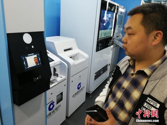 """4月13日,记者探访全国首家""""无人银行""""。无人银行中不仅有大量智能化自助终端,还通过技术与理念创新,将银行各环节的智能服务串联起来,实现整个网点无人化。位于上海市九江路的建设银行九江路支行近日将其重新改造后的一层营业网点对外开放,这里成为国内首家""""无人银行""""网点。中新社记者 康玉湛 摄"""